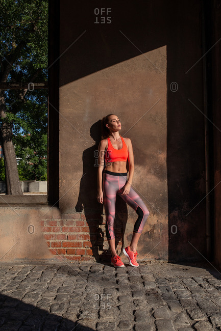 Fit female athlete in activewear leaning on wall of shabby building with eyes closed while standing in city during training
