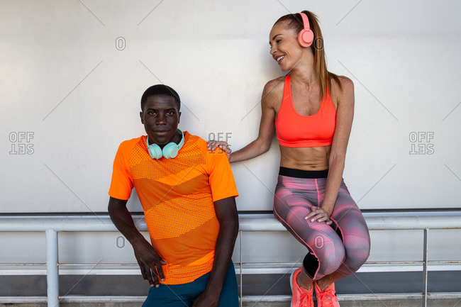 Athletic multiethnic sportswoman and sportsman in activewear relaxing during training in city in summer