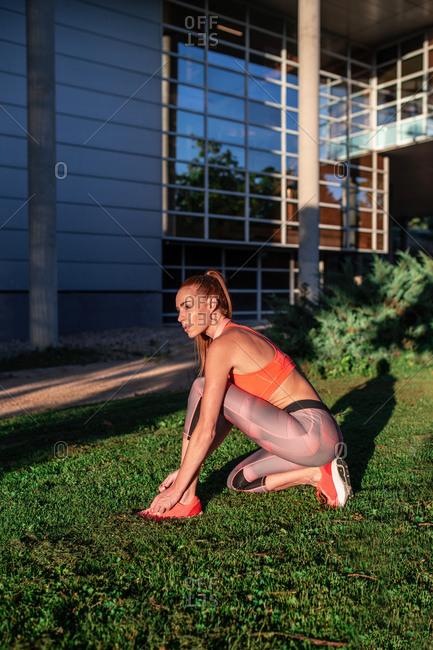 Side view of slim female athlete in summer sportswear tying shoelaces on sneakers during raining in urban park