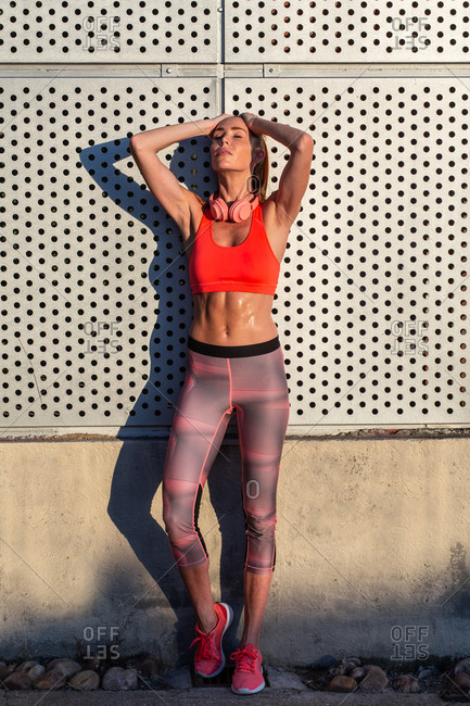 Female athlete in sportswear standing near building in city and relaxing after workout in summer on sunny day with eyes closed