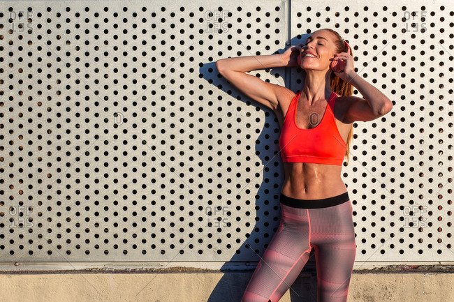 Carefree female runner in sports bra and leggings standing on street and listening to music in headphones during training