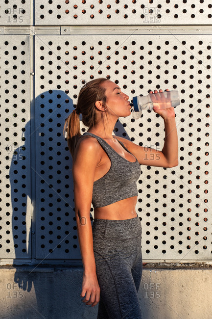 Side view of tired sweaty female runner standing on street on sunny day and enjoying fresh water after active workout