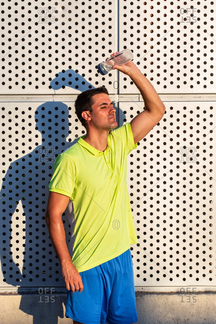 Tired male athlete in sportswear pouring cold water from bottle on head while refreshing after intense training in summer on sunny day