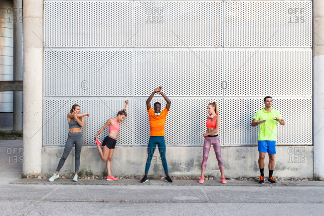 Group of multiracial runners in activewear standing in street and stretching muscles while preparing for training in city