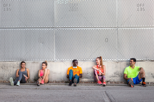 Company of multiethnic sportspeople sitting on street near building and having break during workout in city