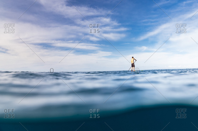 Stand up paddler paddles solo in the ocean of hawaii