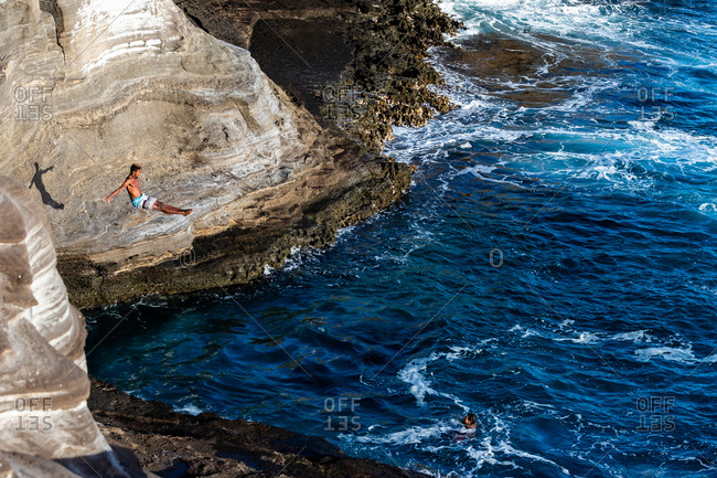 Honolulu, hi, united states - january 23, 2019: male cliff diver dives towards the ocean in oahu, hawaii