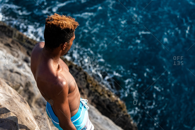 Honolulu, hi, united states - january 23, 2019: male cliff diver looking at the ocean jump zone before diving in oahu