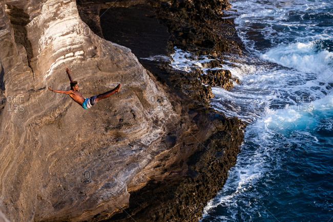 Honolulu, hi, united states - january 23, 2019: male cliff diver in action at the ocean cliffs of oahu, hawaii