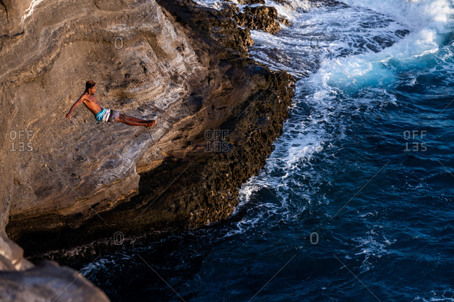 Honolulu, hi, united states - january 23, 2019: athletic male cliff diver jumps into ocean in oahu, hawaii