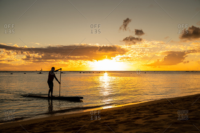 Male stand up paddle boarding drifts to the sand at sunset