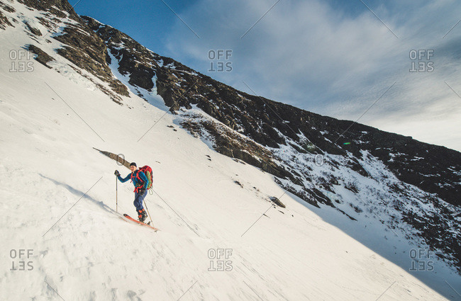 Skier ascends huntington ravine during sunrise in the white mountains