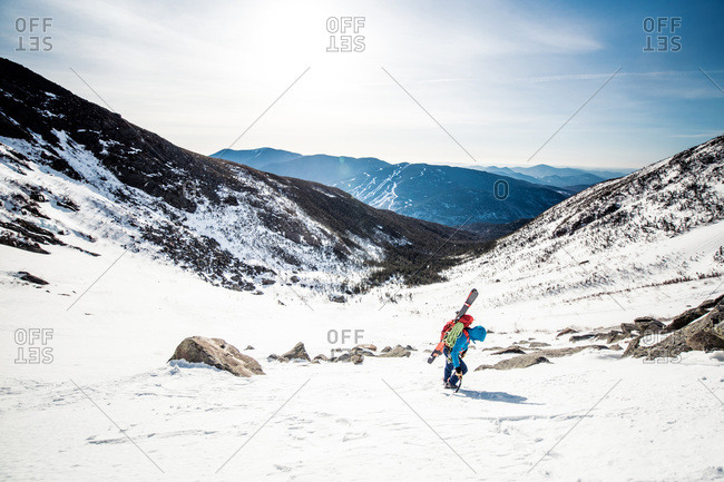 Climber ascending mountain with tools and skis in the white mountains