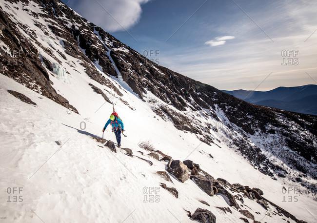 Climber walking through rocks on side of snowy mountain