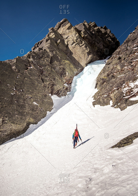 Ice climber walking towards ice gully with skis on back