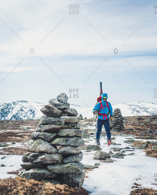 Man following cairns across snow and ice with skis on back