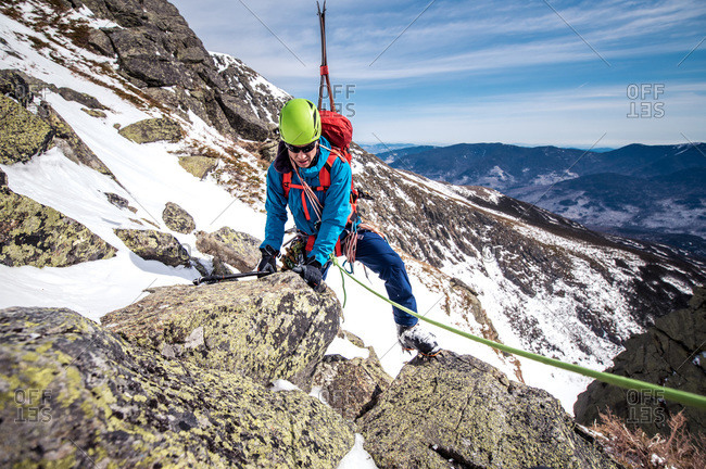 Man climbing rocks above steep snow gully with climbing rope and skis