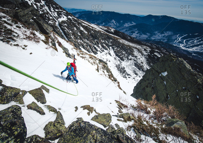 Man climbing steep snow gully with climbing rope and skis
