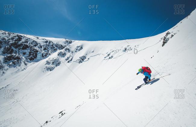 Man skiing down steep terrain in tuckerman ravine, new hampshire