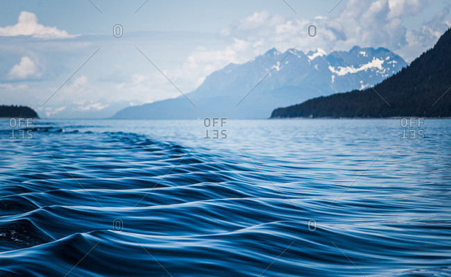 A boat's wake causes ripples and shapes on the water surface in alaska