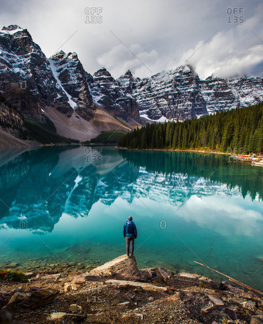 A man standing on a rock on the shore of moraine lake, banff national park