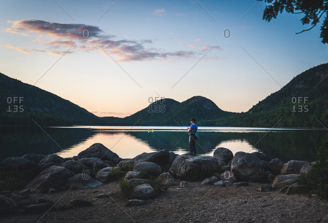 Man standing with fly fishing rod at jordan pond, acadia national park