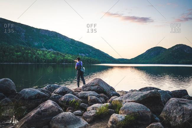 Man fishing at sunset at jordan pond, acadia national park