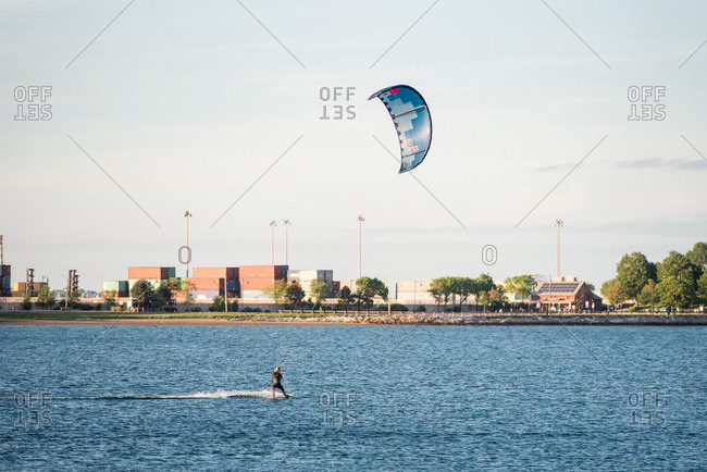 A woman kiteboarding in pleasure bay, boston on a summer afternoon