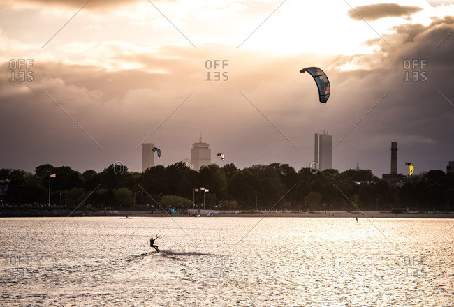 A woman kiteboarding on a summer evening with a dark boston skyline