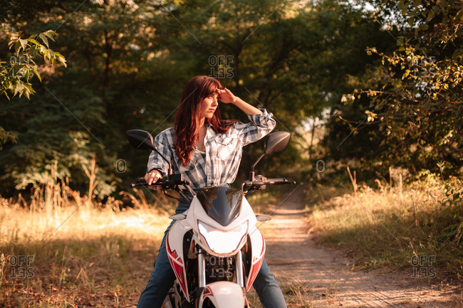Young woman shielding eyes while riding motorcycle on dirt road