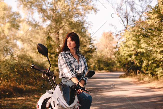 Thoughtful young woman looking away while sitting on motorcycle