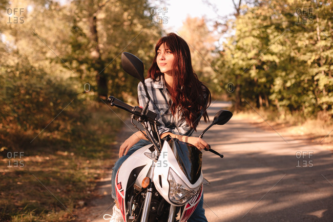 Happy confident young woman looking away while sitting on motorcycle