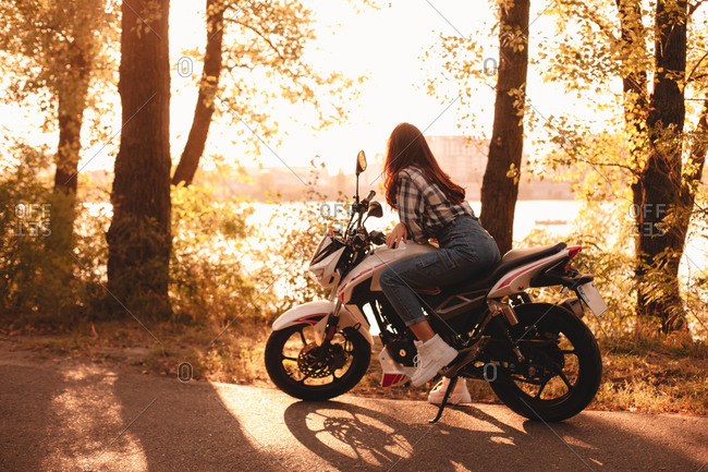 Woman looking at view while sitting on motorcycle by river