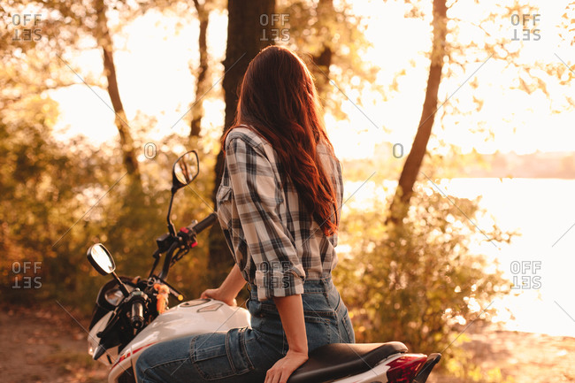Woman looking at view while sitting on motorcycle relaxing by river