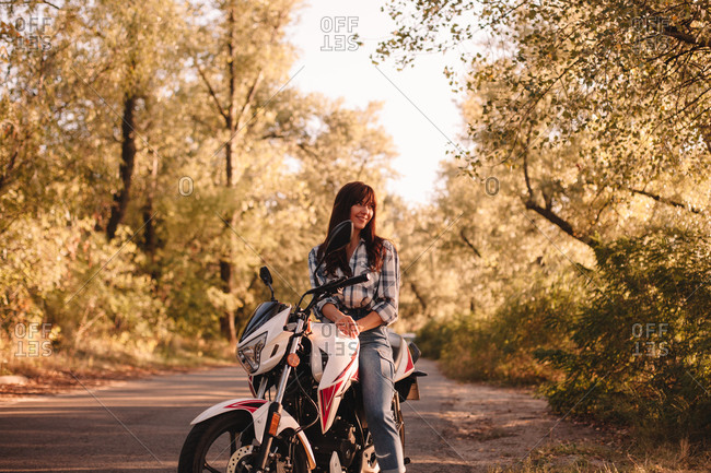 Smiling young woman sitting on motorcycle on country road amidst trees