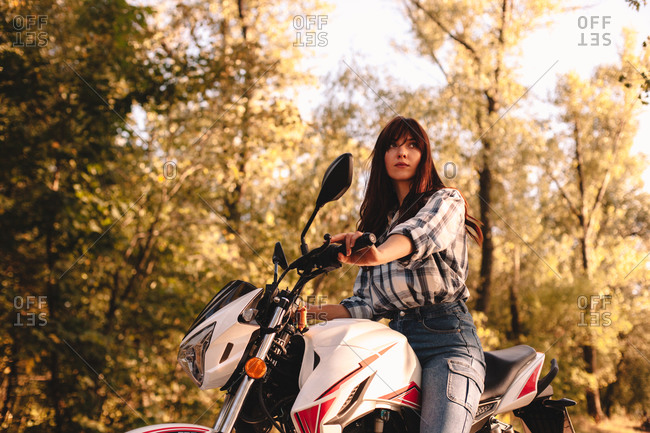 Confident young woman riding motorcycle amidst trees in forest