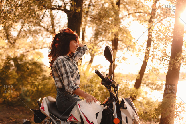 Happy young woman relaxing sitting on motorcycle amidst trees
