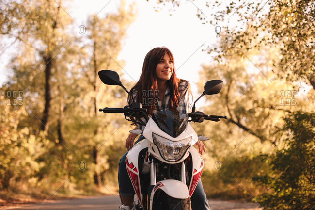 Smiling confident young woman sitting on motorcycle on country road