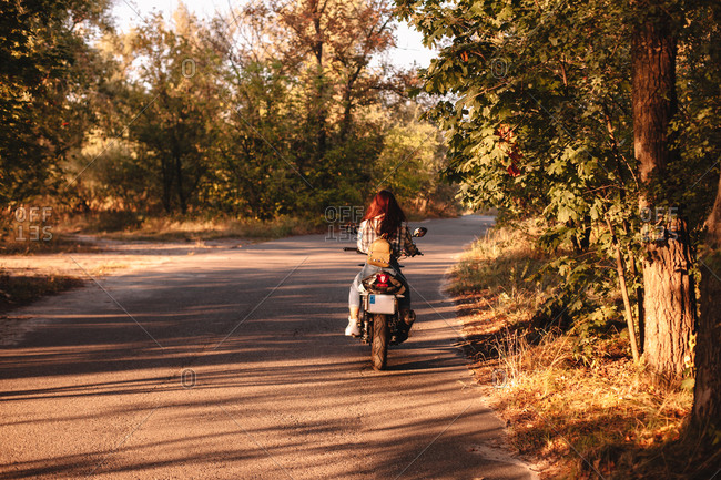 Back view of woman riding motorcycle on country road amidst trees