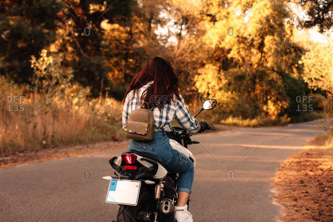 Back view of woman riding motorcycle on country road in forest