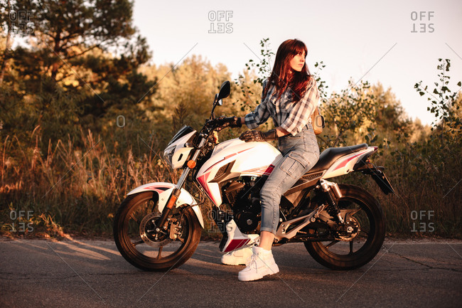 Confident woman sitting on motorcycle on country road looking back