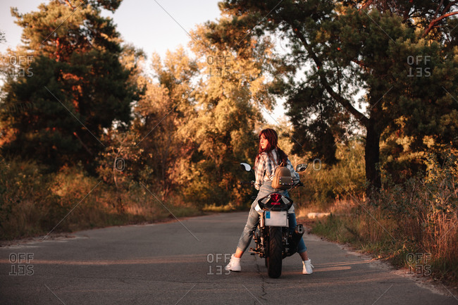 Young woman looking at sunset sitting on motorcycle on country road