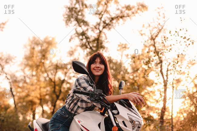 Portrait of happy young woman sitting on motorcycle amidst trees