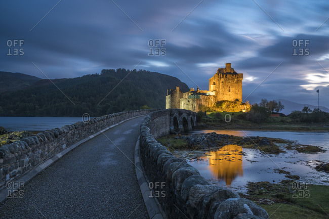 Illuminated eilean donan castle against cloudy sky at dusk, scotland, uk