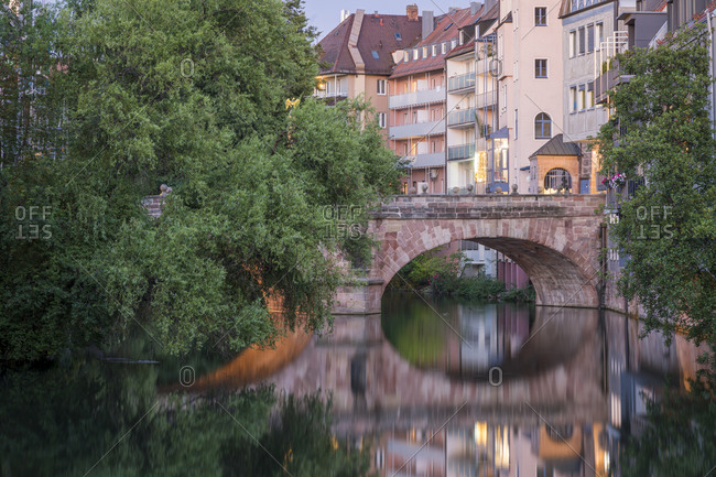 Residential buildings and arch of karlsbrucke bridge on pegnitz river at dusk, nuremberg, germany