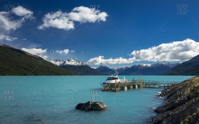Tourist boat moored at jetty on shore of lago argentino near perito moreno glacier, argentina