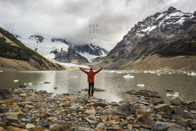 Rear view of young man in red jacket standing with open arms by laguna torre, los glaciares national park, el chalten, patagonia, argentina
