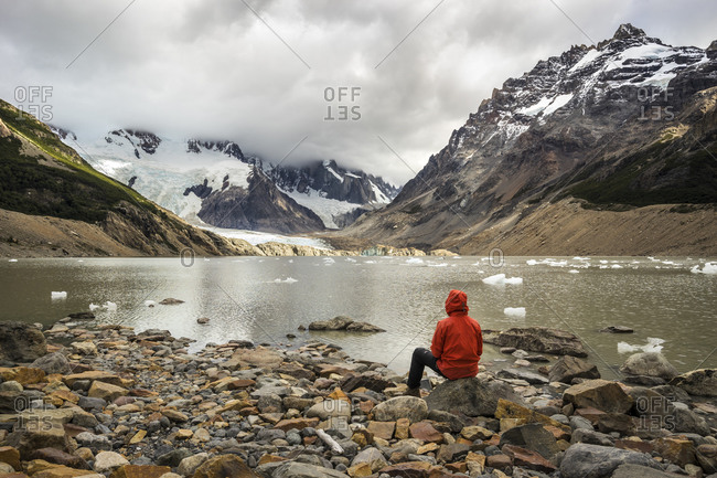 Rear view of young man in red jacket sitting by laguna torre, los glaciares national park, el chalten, patagonia, argentina