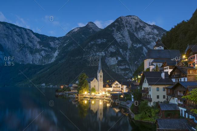 Evangelical parish church by hallstatter see against mountains at twilight, hallstatt, austria