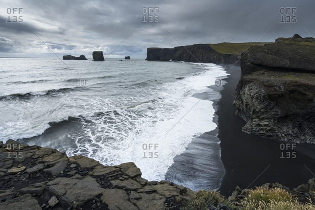 Scenic view of kirkjufjara beach and dyrholaey peninsula against cloudy sky, south iceland, iceland